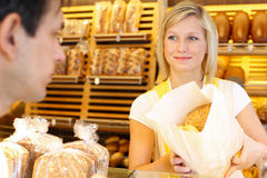 Baker's shop shopkeeper gives bread to customer Stock Images