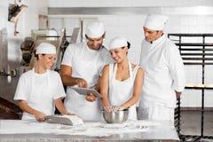Baker's Using Digital Tablet Together At Table Stock Image
