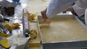 Baker scoring and perforating tray of dough in industrial kitchn stock video footage