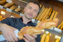 Baker selling fresh bread baguettes in bakery royalty free stock photography