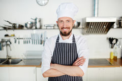 Baker-shop owner. Happy young pastry-baker in the kitchen Royalty Free Stock Photography
