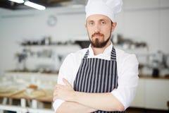 Baker-shop worker. Bearded baker in uniform looking at camera Stock Photos