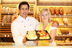 Baker and shopkeeper in bakery with tablet of cake. Baker and shopkeeper in bakery present tablet full of cake Stock Image