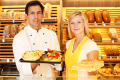 Baker and shopkeeper present pastry Royalty Free Stock Photo