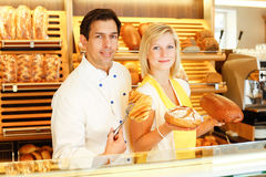 Baker and shopkeeper present pastry Royalty Free Stock Photos