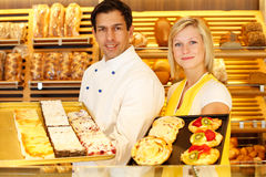 Baker and shopkeeper present pastry Royalty Free Stock Images