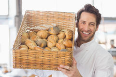 Baker showing basket of bread. In the kitchen of the bakery Stock Photography