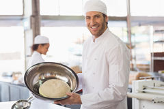 Baker showing dough in mixing bowl Stock Photo