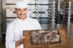 Baker showing freshly baked brownie Royalty Free Stock Image