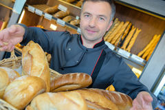 Baker showing variety breads Royalty Free Stock Images