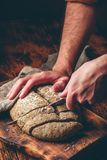 Baker slices loaf of homemade rye bread. On cutting board royalty free stock photography