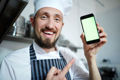 Baker with smartphone. Bearded baker pointing at smartphone in his hand Royalty Free Stock Photo