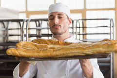Baker smelling freshly baked baguettes Stock Photos