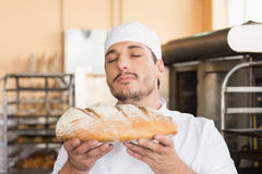 Baker smelling freshly baked loaf Stock Images