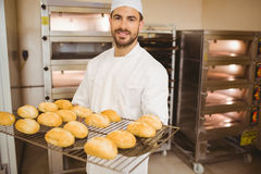 Baker smiling at camera holding rack of rolls Stock Images