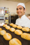 Baker smiling at camera holding tray of rolls Stock Photography