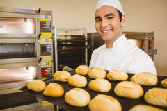 Baker smiling at camera holding tray of rolls Stock Image
