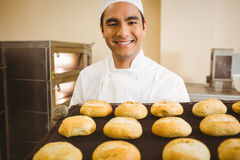 Baker smiling at camera holding tray of rolls Royalty Free Stock Photography