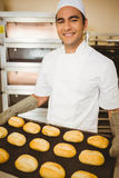 Baker smiling at camera holding tray of rolls Royalty Free Stock Image
