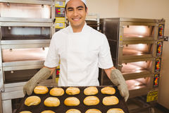 Baker smiling at camera holding tray of rolls Royalty Free Stock Photos