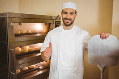 Baker smiling at camera beside oven Royalty Free Stock Images