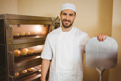 Baker smiling at camera beside oven Stock Images