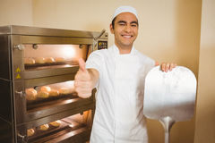 Baker smiling at camera beside oven Stock Photos