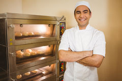 Baker smiling at camera beside oven. In a commercial kitchen Stock Photography