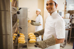 Baker smiling at camera taking rolls out of oven Royalty Free Stock Photos