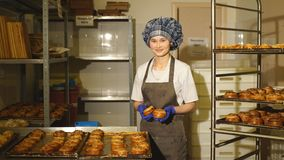 Baker standing in his bakery in the morning and is baking bread or buns. Baker smiling at camera holding rack of rolls in a commercial kitchen stock video