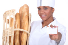 Baker. Stood by a basket of bread stock photos