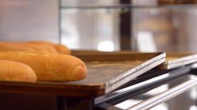 Baker take baguette on shelf stock footage