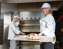 Baker with tasty loaf of bread on a peel Stock Photography