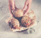 Baker tenant des petits pains de pain frais avec la graine de tournesol Image stock