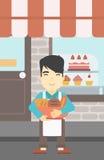 Baker tenant le panier avec des produits de boulangerie Image libre de droits