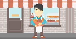 Baker tenant le panier avec des produits de boulangerie Photo stock