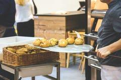Baker tenant les scones fraîchement cuites au four en four bifurquent images stock