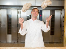 Baker throwing dough into air in bakehouse. Baker throwing dough into the air in bakery Stock Photography