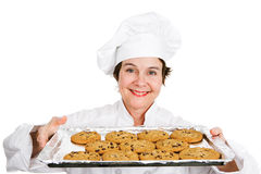 Baker with Tray of Cookies. Cute female chef in her uniform, holding up a tray of delicious, freshly baked chocolate chip cookies.  Isolated on white background Royalty Free Stock Photography