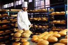 Baker trekt zich van het oven verse brood terug stock foto's