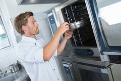 Baker using oven in kitchen bakery. Baker using an oven in the kitchen of the bakery Royalty Free Stock Photography