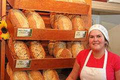 Baker and a variety of bread. Baker showing her variety of bread loaves Stock Photo