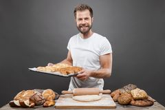 Baker with a variety of delicious freshly baked bread and pastry Royalty Free Stock Image