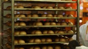 Baker verwijdert een rek van brood uit een oven stock videobeelden
