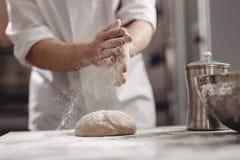 Baker voegt bloem aan deeg op de lijst in de bakkerij toe stock foto's