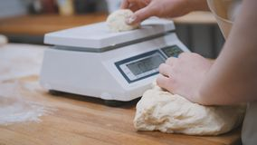 Baker weighing dough for baking stock images