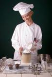 Baker weighing flour. Action capture of a uniformed female Baker weighing baking flour in a scale Stock Photos