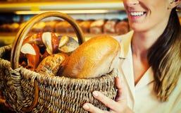 Baker woman in backer selling bread in basket Royalty Free Stock Photos