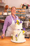 Baker Woman decorates Wedding Cake Royalty Free Stock Images