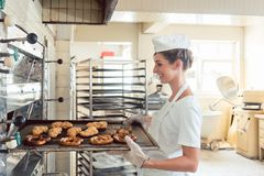 Baker woman getting bakery products out of oven Stock Photo